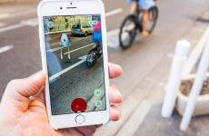 Antibes, France - July 31, 2016: A man plays PokŽmon Go on the side of a city street as traffic passes by. The game player is in the process of collecting a Tentacool PokŽmon that hovers in the middle of the road.